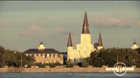 A sunrise shot of Jackson Square from across Mississippi River with the stately St. Louis Cathedaral.